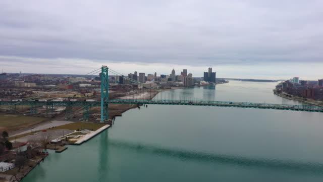 flying towards the ambassador bridge viewing detroit - detroit river stock-videos und b-roll-filmmaterial