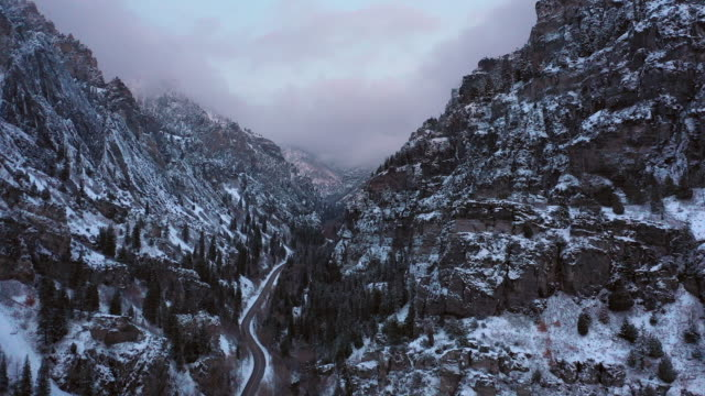 vídeos de stock, filmes e b-roll de flying up rugged canyon in winter at dusk following road - utah
