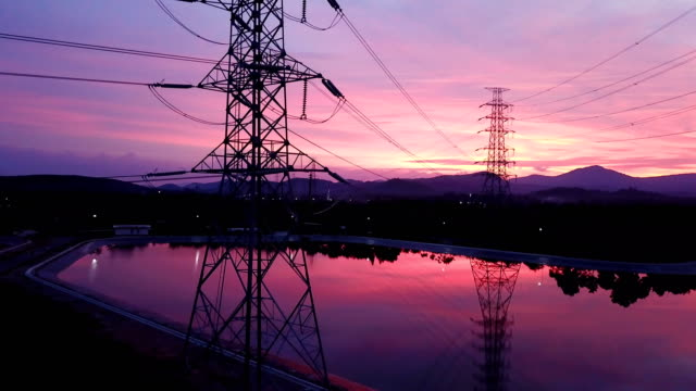 aerial: flying up the high voltage electricity tower at sunset - power supply stock videos & royalty-free footage