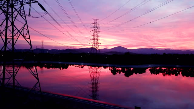 aerial: flying up the high voltage electricity tower at sunset - electricity pylon stock videos & royalty-free footage