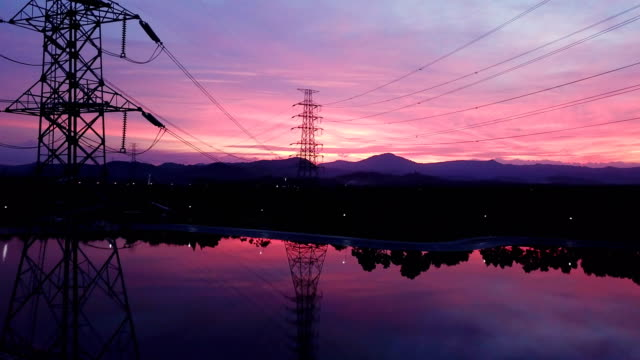 vídeos de stock e filmes b-roll de aerial: flying up the high voltage electricity tower at sunset - alta voltagem