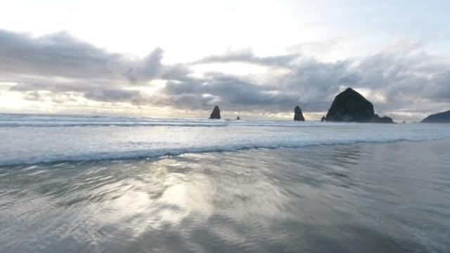 flyover aerial drone establishing shot of cannon beach and haystack rock sea stack. - oregon coast stock videos & royalty-free footage