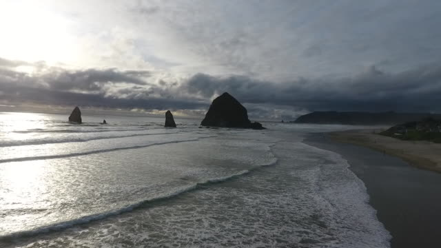 flyover aerial drone establishing shot of cannon beach and haystack rock sea stack. - cannon beach stock videos & royalty-free footage