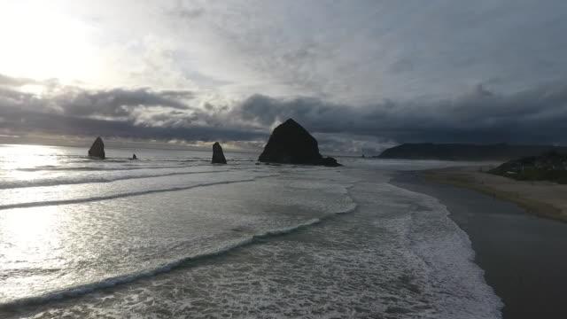 vídeos de stock, filmes e b-roll de flyover aerial drone establishing shot of cannon beach and haystack rock sea stack. - costa de oregon
