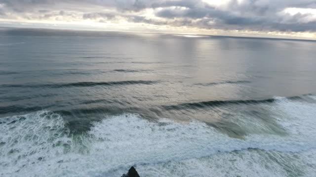 flyover aerial drone establishing shot of cannon beach and haystack rock sea stack - oregon coast stock videos & royalty-free footage