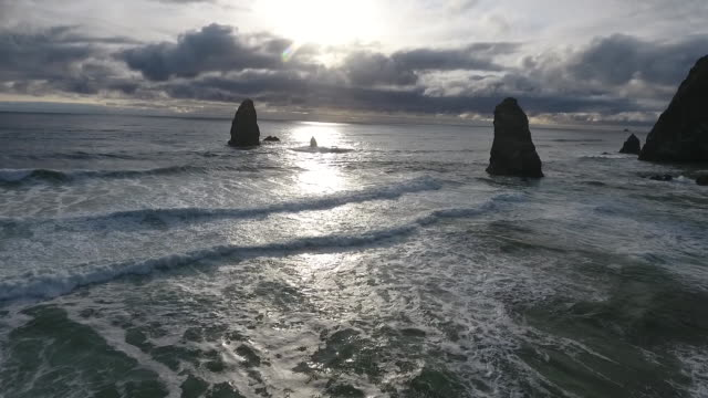 vídeos de stock, filmes e b-roll de flyover aerial drone establishing shot of cannon beach waves and haystack rock sea stack. - costa de oregon