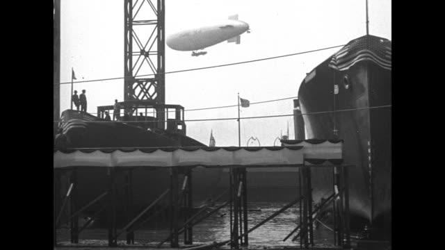 flyover ships in dry dock in shipyard / airship passes in background as ships stand at dock / vs shipyard with ships under construction in... - 造船所の労働者点の映像素材/bロール