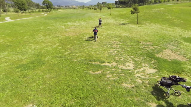 flythrough over golf course accompanying three golfers - golfer stock videos and b-roll footage