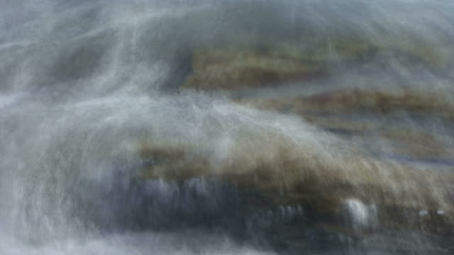 foam and mist washes over slate colored ocean stone. - miglioramento digitale video stock e b–roll