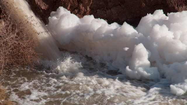ms foam from factory pollution floating on a river - water pollution stock videos & royalty-free footage