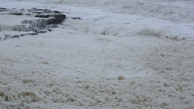 Foam wipped up by storm waves blows ashore at Craster on the Northumberland coast. Taken on Monday 4th January 2016