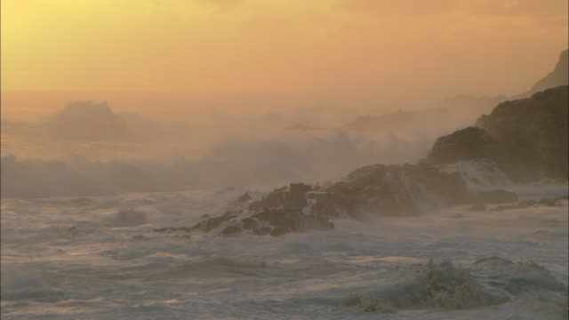 Foaming breakers crash onto rocky shore at sunrise, South Africa