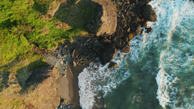 vidéos et rushes de vagues moussantes s'écraser sur les rochers et les falaises - top down drone shot - falaise