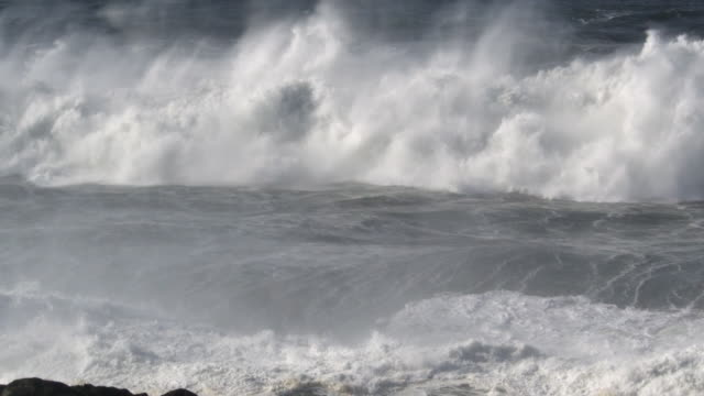 Foaming waves overtop a rocky shoreline and rain down a shower of water drops