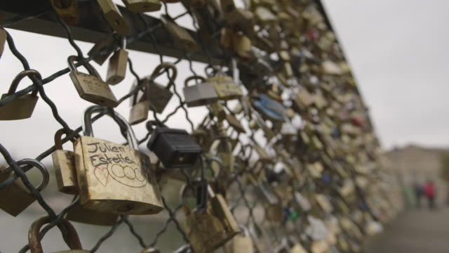 stockvideo's en b-roll-footage met focus on a padlock bearing the names julien and estelle on the pont des arts in paris, which became synonymous with a trend for 'love locks', 2013. - oneindigheid