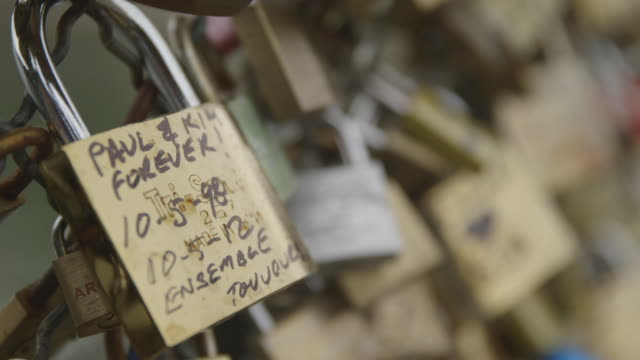 Focus on a padlock declaring love between Paul and Kim on the Pont des Arts in Paris, France, 2013.
