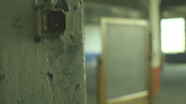 Focus on a shabby old-fashioned light-switch in the foreground, with free-standing blackboard standing in an empty warehouse in the background, with natural daylight pouring in through large windows, UK.