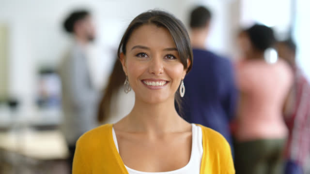 focus on background of people in an office talking and then focus on foreground of a young creative smiling at the camera - etnia latino americana video stock e b–roll