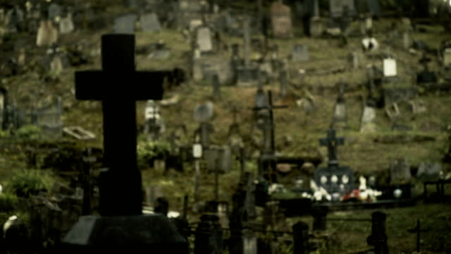 vidéos et rushes de focus on cross in a creepy cemetery - pierre tombale