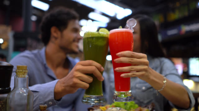 focus on foreground of couple enjoying food and toasting with drinks - anniversary stock videos & royalty-free footage