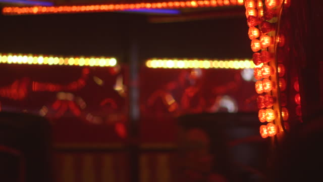 vídeos y material grabado en eventos de stock de focus on the red light bulbs of the central 'axle' of a fairground waltzer ride as waltzer cars whizz and spin past, uk. - náusea