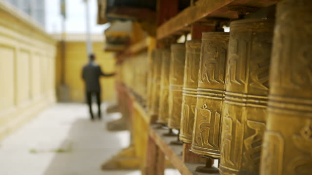 focus out: full length rear view of woman rolling prayer wheel at buddhist temple - ulaanbaatar, mongolia - ulan bator stock videos & royalty-free footage