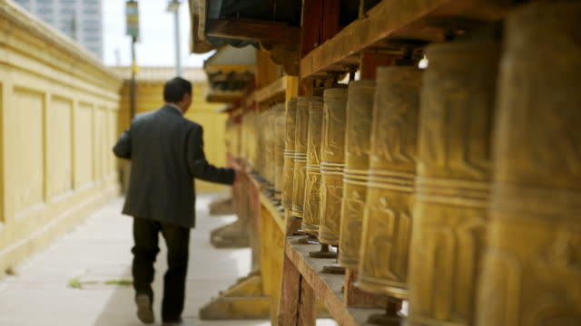 focus out: rear view of man rolling prayer wheel at buddhist temple - ulaanbaatar, mongolia - independent mongolia stock videos & royalty-free footage