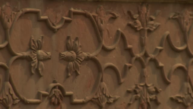 Focus pull and pan across an exterior wall decorated with a patterned relief in Agra Fort, India.