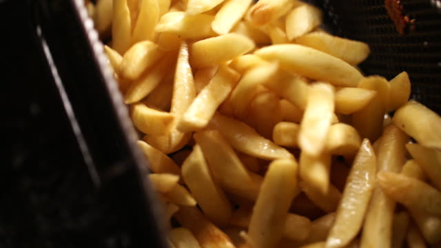 Focus Pull CU SLO MO of chips in fryer/ Johannesburg/ South Africa