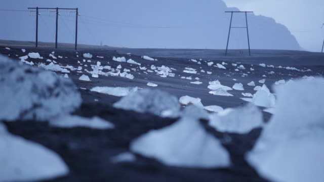Focus pull from lumps of ice sitting incongruously on a beach onto telegraph poles, Iceland.