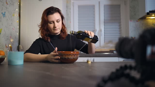 focus shift: young female blogger pours olive oil in salad while recording a tutorial - sich verschönern stock-videos und b-roll-filmmaterial