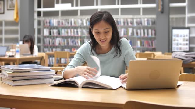 本を読む図書館で焦点を当てたアジアの女性若い学生 - 公共図書館点の映像素材/bロール