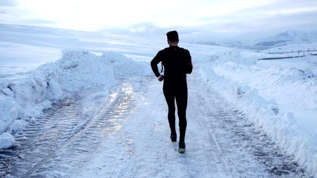 fokussierte athlet läuft auf schnee - marathon stock-videos und b-roll-filmmaterial