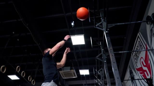 vídeos y material grabado en eventos de stock de atleta enfocado lanzando una pelota de medicina - pelota de ejercicio