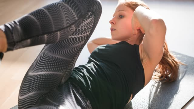 focused athletic woman doing abdominal exercises to strengthen her core - pilates stock videos and b-roll footage