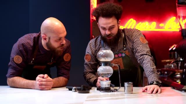 focused baristas making coffee at a bar - peluria del viso video stock e b–roll