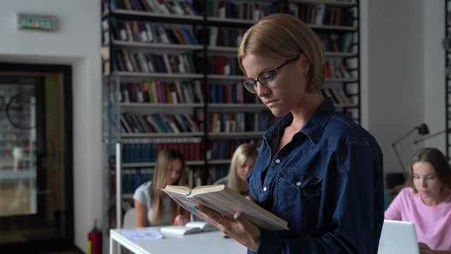 Fokussierter schöner Schüler, der ein Buch in der Bibliothek liest