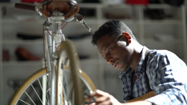 focused black man repairing a bicycle on a table and using a tool - aggiustare video stock e b–roll