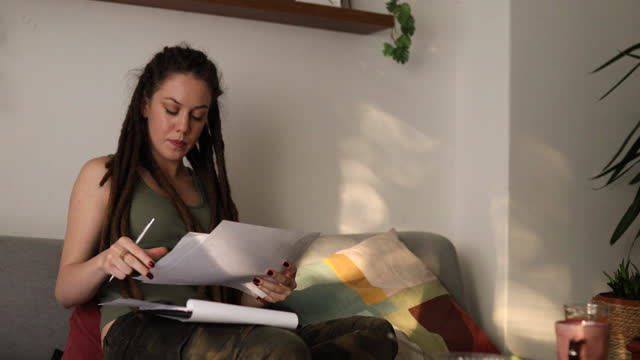 focused business woman, reading statistic from presentation on her laptop, while arranges the monthly financial report, from her home office due home isolation - financial advisor stock videos & royalty-free footage