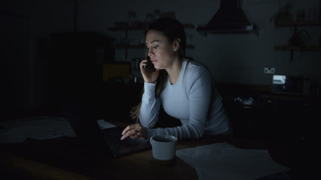focused business woman working on laptop late at home while on a phone conversation - using laptop stock videos & royalty-free footage