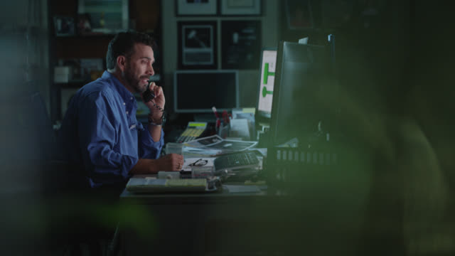 focused businessman dials phone number, talks on phone while sitting at office desk - desk stock videos & royalty-free footage