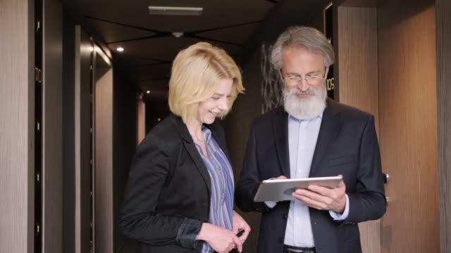 vidéos et rushes de hommes d'affaires concentrés utilisant la tablette numérique dans le couloir d'hôtel - seniornaute