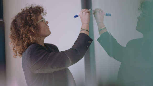 focused businesswoman reads and writes notes on whiteboard - entscheidung stock-videos und b-roll-filmmaterial