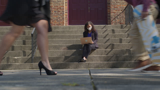 focused businesswoman sits on a staircase as she works on her laptop as pedestrians pass by her - walkable city stock videos & royalty-free footage