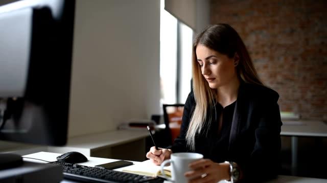 stockvideo's en b-roll-footage met gerichte creatieve zakenvrouw, het maken van notities op computer in bureau - haar naar achteren