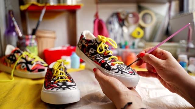 スニーカーに防水塗料を適用する焦点を当てた創造的な女性アーティスト - 不完全な美しさ点の映像素材/bロール