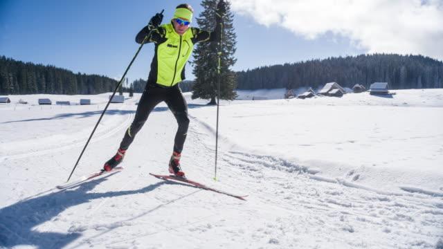 Focused cross country skier skate skiing uphill