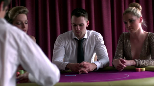 stockvideo's en b-roll-footage met focused dealer dealing cards at the poker table in the casino - overhemd en stropdas