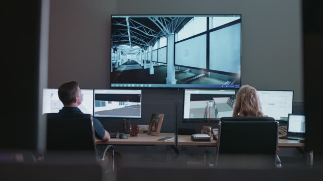 focused design professionals inspect 3d model blueprints for a new building construction on thier computer monitors - graphical user interface stock videos & royalty-free footage