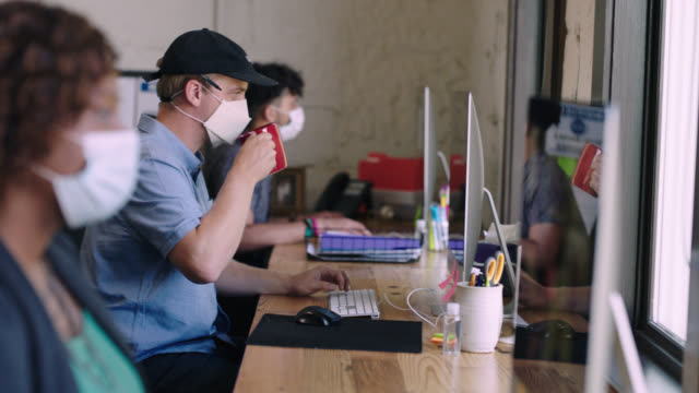 focused employee working on computer in office attempts to drink coffee, forgetting that he is wearing face mask - employee stock videos & royalty-free footage